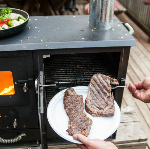a wood burning portable grill cooking a steak